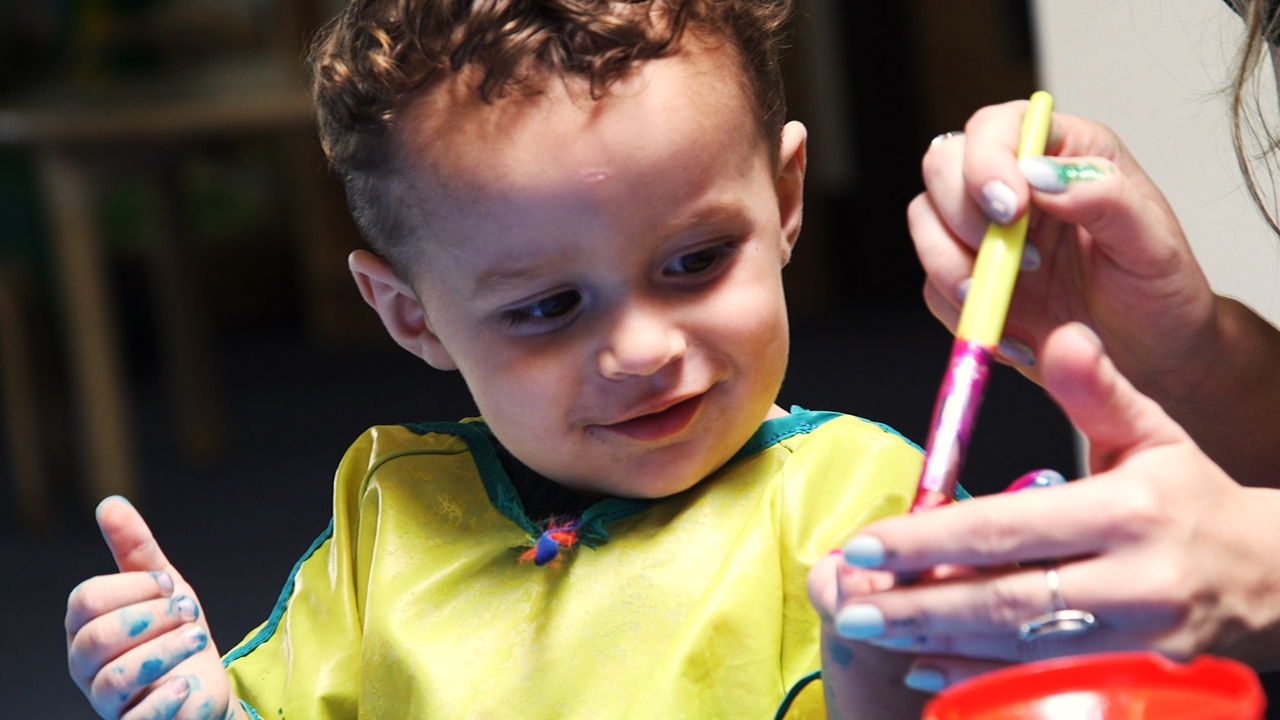 Boy finger painting at LifeWorks NW's Children's Relief Nursery
